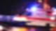 Ein Rettungswagen fährt schnell vorüber. Er ist unscharf, weil er so schnell fährt, das Blaulicht ist an.